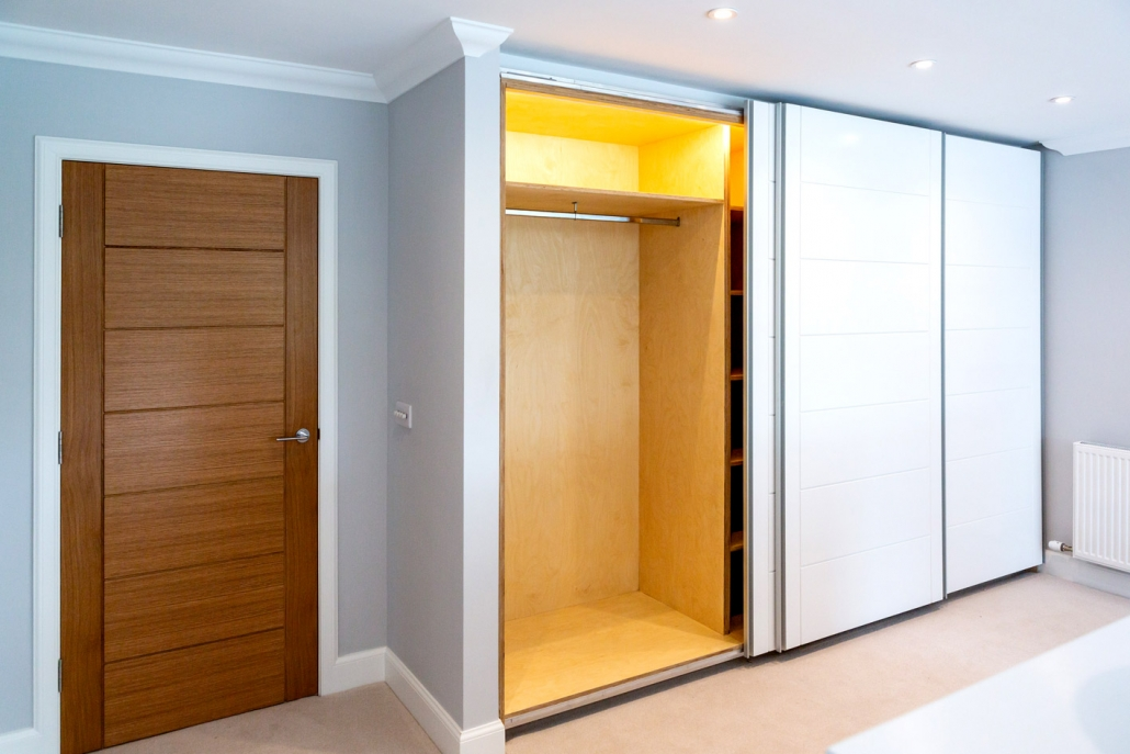 Birch plywood bespoke wardrobes with interior lighting.