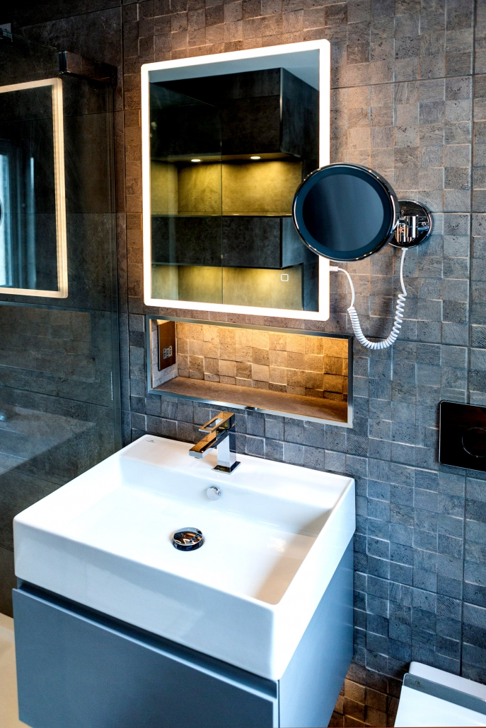 En-suite bathroom installation with Porcelanosa tiles and LED lit mirror.