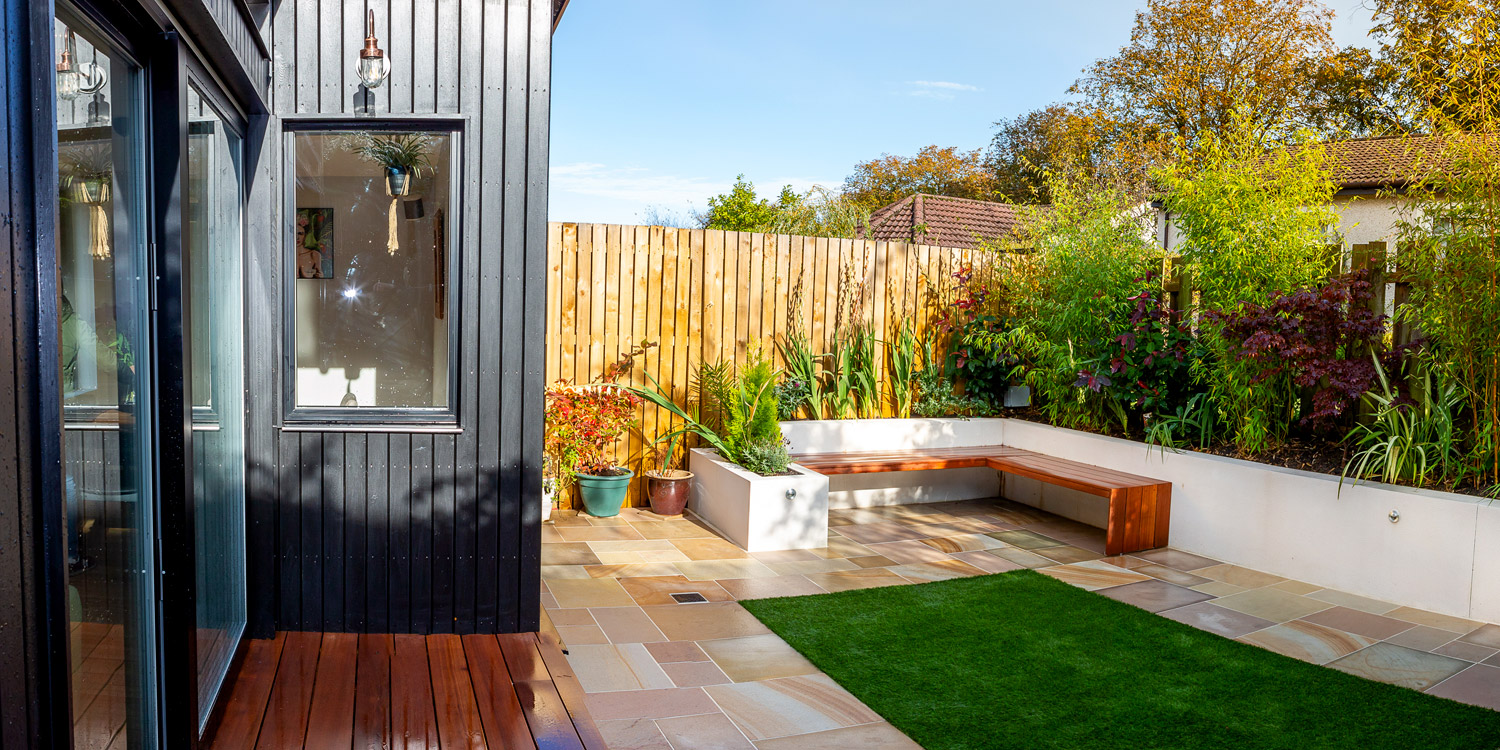Extension clad with black Siberian larch. Seating is yellow Balau decking.